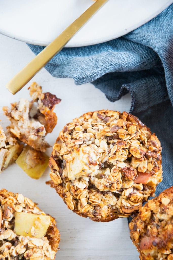 Ein Oatmeal Muffin mit Apfel und Nüssen in der Nahaufnahme von oben auf weißem Untergrund mit blauem Leinentuch. Stücke eines zweiten Muffins liegen daneben.
