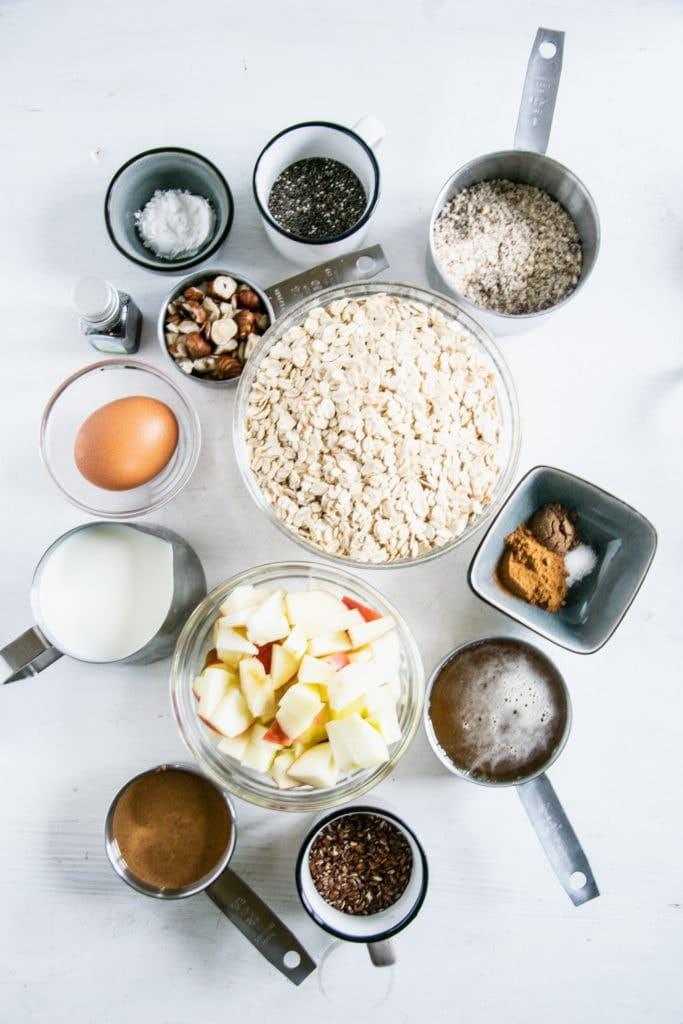 Zutaten für Oatmeal Muffins mit Apfel und Nüssen in Schüsseln und Cups. Flatlay auf weißem Untergrund.