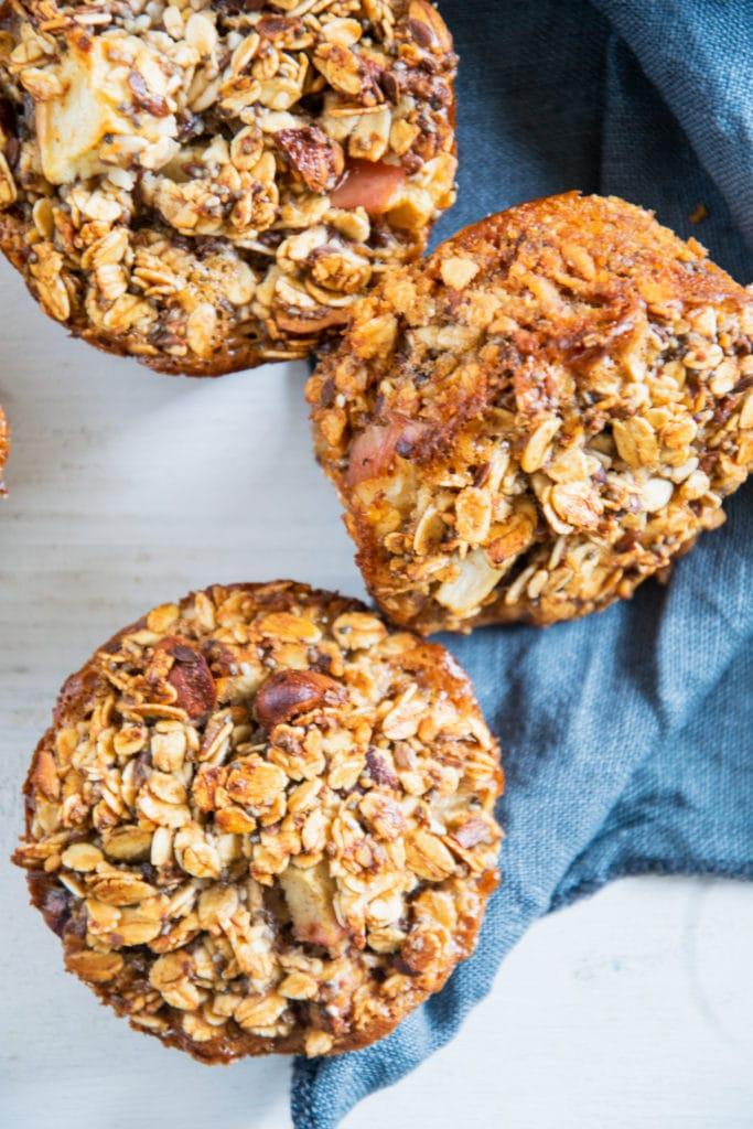 Oatmeal Muffins mit Apfel und Nüssen in der Nahaufnahme von oben auf weißem Untergrund mit blauem Leinentuch. Von zwei Muffins ist die Oberfläche sichtbar, der dritte liegt auf der Seite.