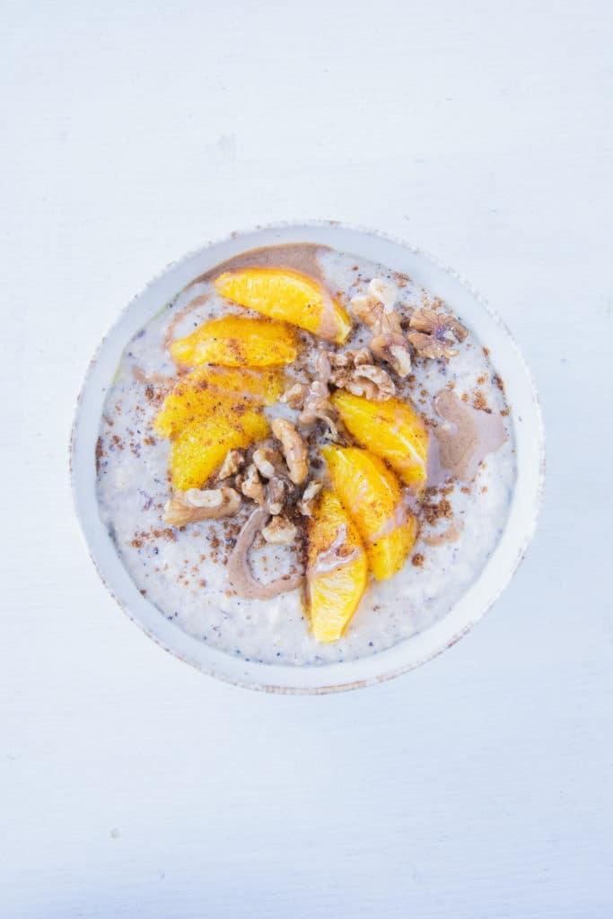 Porridge getoppt mit Orangenspalten, Walnüssen, Lebkuchengewürz und Haselnussmus. Aufnahme von oben.