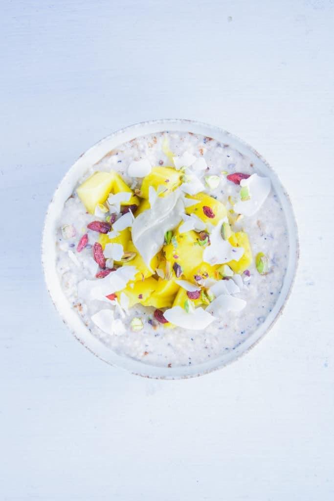 Porridge getoppt mit Mangeowürfeln, Gojibeeren, Kokoschips, Pistazien, Hanfsamen und Cashewmus. Aufnahme von oben.