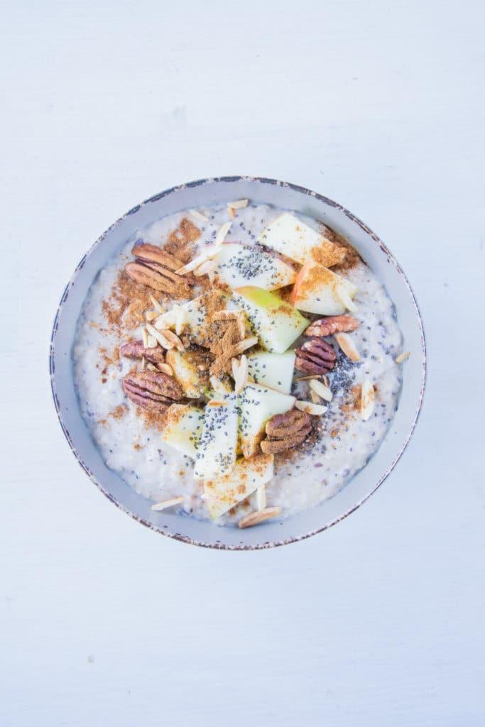 Porridge getoppt mit Apfel, Mandelsplittern, Pekannusskernen, Zimt und Chiasamen