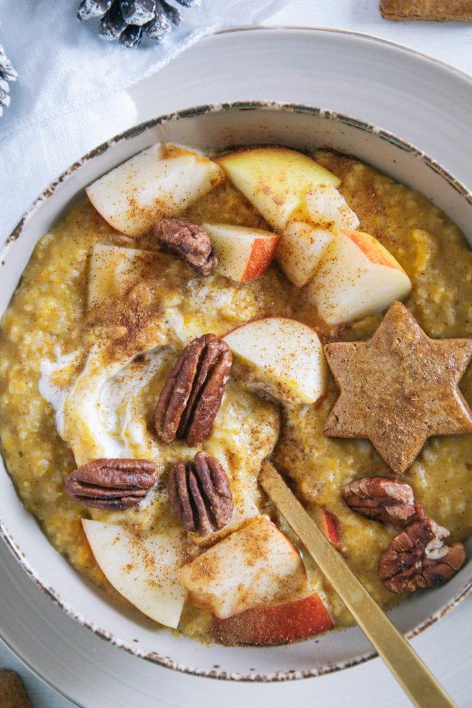 Kürbis-Porridge mit einem Topping aus Apfelstücken, Pekannüssen, einem Lebkuchenstern und Zimt. Goldener Apfel im Porridge. Nahaufnahme von oben