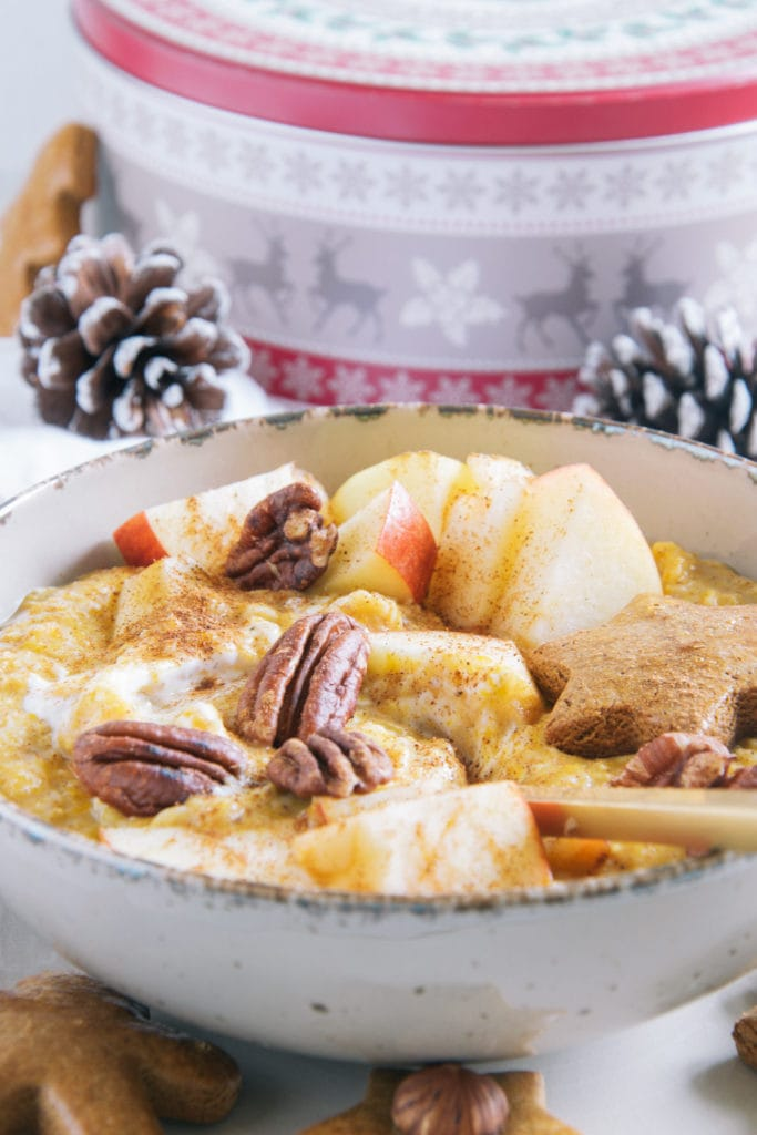 Kürbis-Porridge mit einem Topping aus Apfelstücken, Pekannüssen, einem Lebkuchenstern und Zimt. Goldener Apfel im Porridge. Aufnahme im 45-Grad-Winkel mit einer Keksdose und Zapfen im Hintergrund.