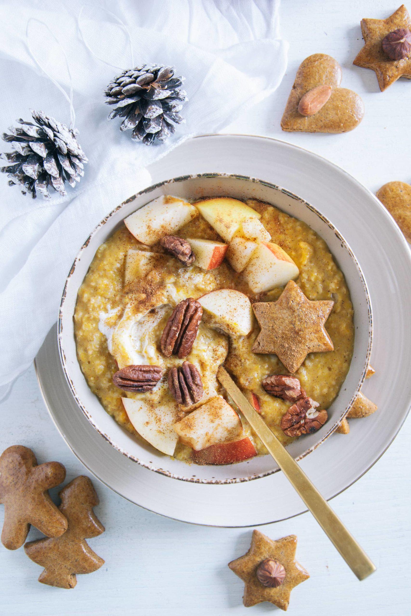 Kürbis-Porridge mit einem Topping aus Apfelstücken, Pekannüssen, einem Lebkuchenstern und Zimt. Goldener Apfel im Porridge. Braune Schüssel auf beigem Teller und weißem Untergrund. Dekoriert mit einem weißen Leinentuch und Zapfen.