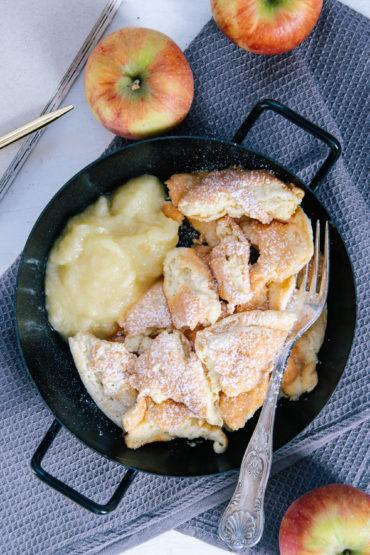 Protein-Kaiserschmarrn mit Apfelmus in einer schwarzen Servierpfanne auf einem dunkelblauen Leinentuch. Äpfel als Dekoration. Von oben fotografiert.