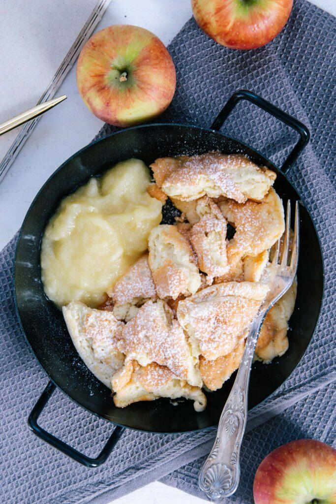 Protein-Kaiserschmarrn mit Apfelmus in einer schwarzen Servierpfanne auf einem grauen Leinentuch. Äpfel als Dekoration. Von oben fotografiert.