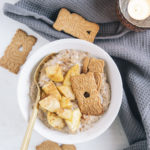 Spekulatius-Porridge mit Bratapfel in einer weißen Schüssel mit goldenem Löffel. Aufnahme von oben. Graues Leinentuch, Kerze und weitere Spekulatiuskekse als Dekoration.