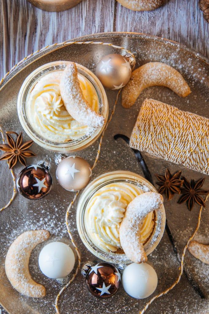 Vanillekipferl-Cheesecake-Dessert mit Mandelnougat auf einem goldenen Teller mit einer Rolle Glitzergarn als Dekoration. Aufnahme von oben.