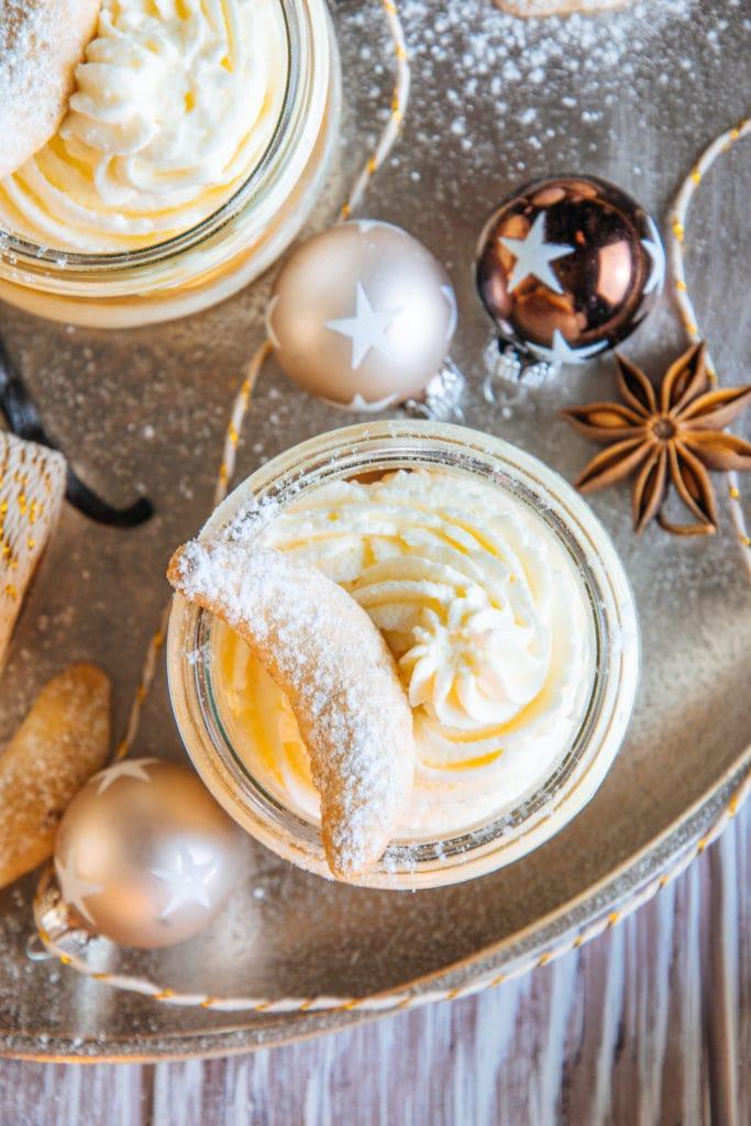Nahaufnahme von oben von Vanillekipferl-Cheesecake-Dessert mit Mandelnougat. Die Sahne im Glas und das Vanillekipferl als Topping sind detailliert sichtbar, daneben zwei kleine Christbaumkugeln mit Sternen und ein Anisstern.
