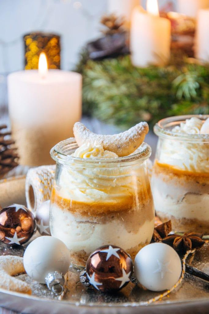 Zwei Gläser Vanillekipferl-Cheesecake-Dessert mit Mandelnougat im kleinen Tulpenglas fast bildfüllend platziert und knapp über Augenhöhe fotografiert. Im Hintergrund brennende Kerzen vom Adventkranz. Das Bild strahlt Wärme und Gemütlichkeit aus.