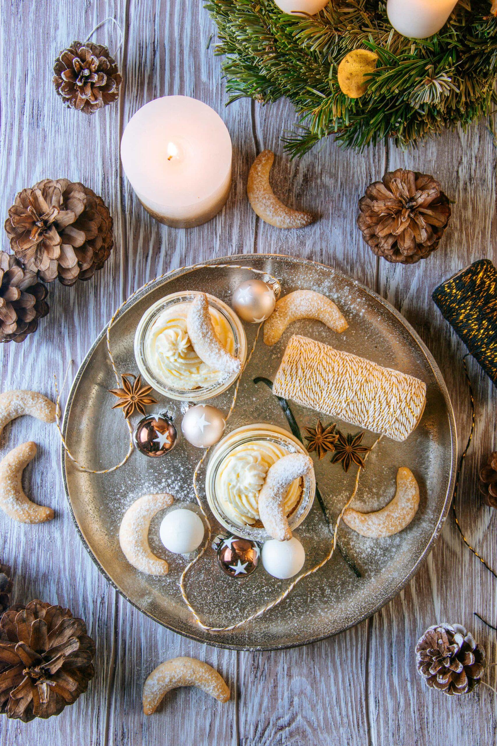 Zwei Gläser Vanillekipferl-Cheesecake-Dessert mit Mandelnougat auf einem großen goldenen Teller, verziert mit Vanillekipferln, kleinen Christbaumkugeln, Glitzergarn und Anissternen. Aufnahme von oben auf braunem Untergrund im rustikalen Stil.