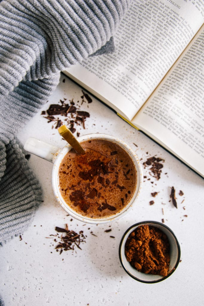 Eine Tasse Kakao von oben fotografiert auf hellem Untergrund mit Kakaopulver darauf. Goldener Löffel in der Tasse, aufgeschlagenes Buch und grauer Pullover daneben.