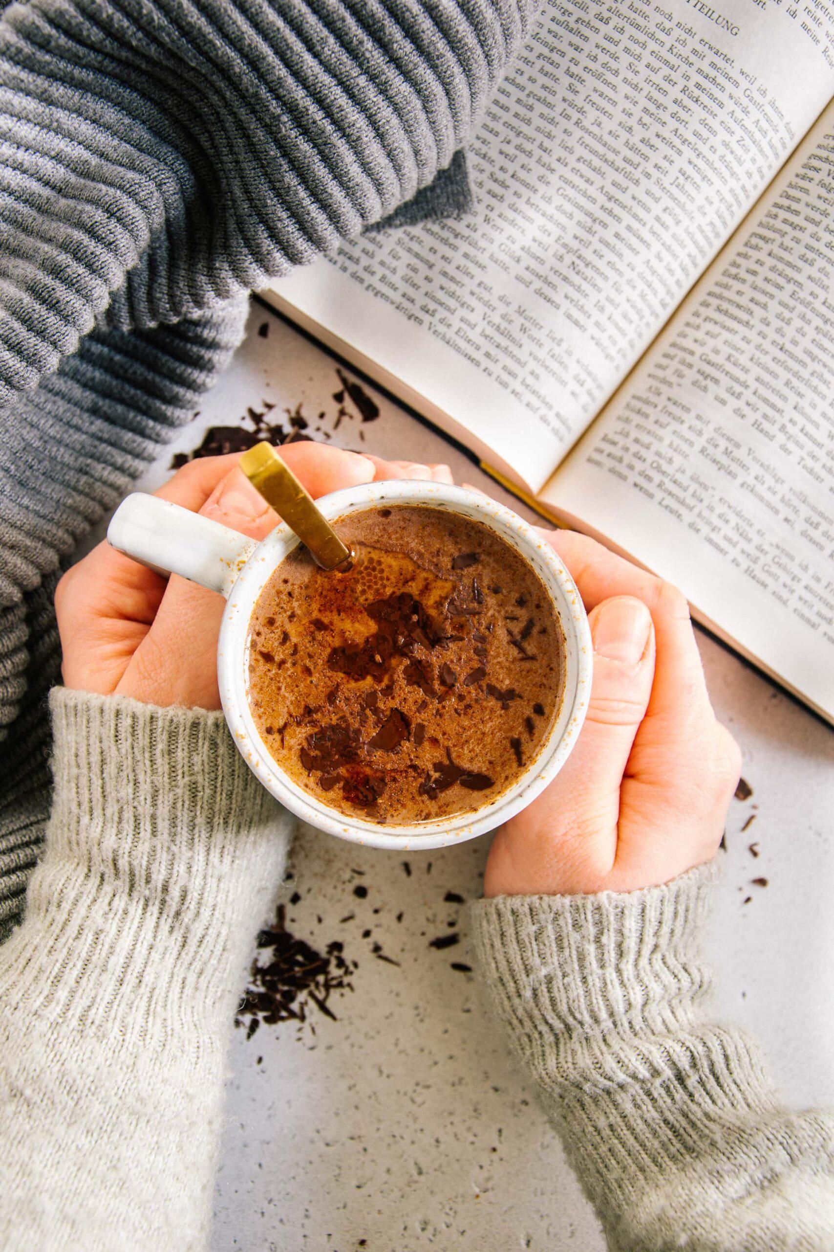 Zwei Hände umschließen eine Tasse Kakao. Aufnahme von oben mit aufgeschlagenem Buch daneben. Warme Farben und hyggeliger Stil.