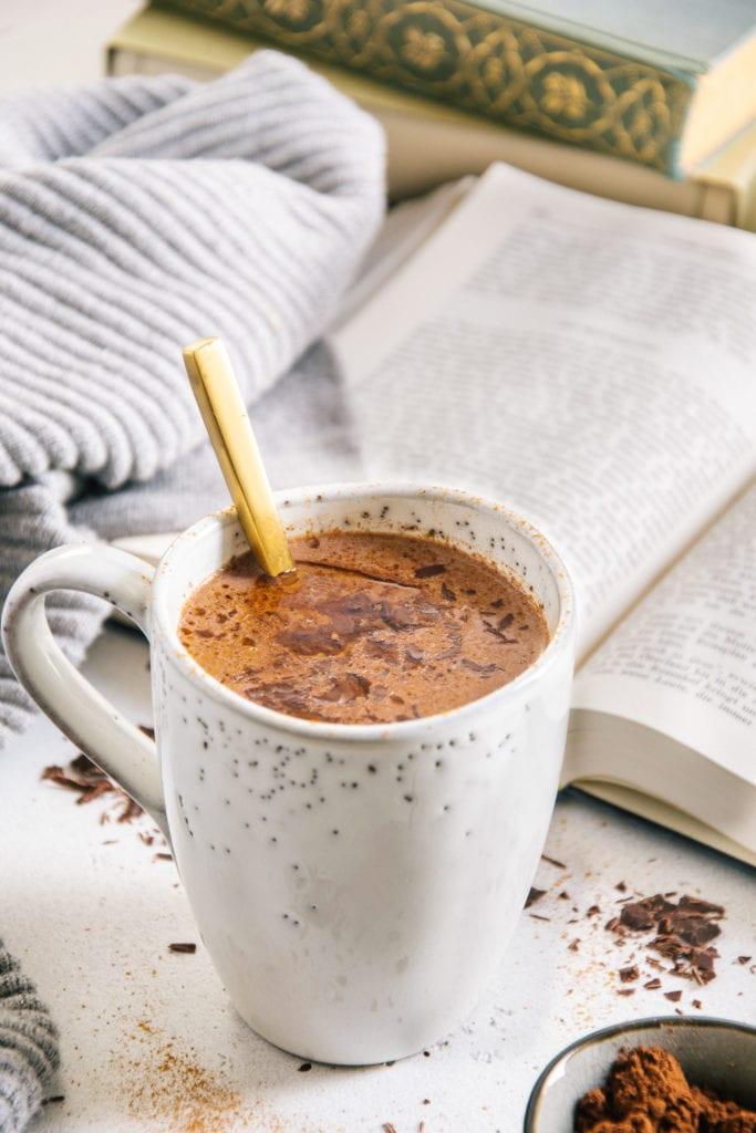 Kakao mit geschmolzener Schokolade und Kokosöl an der Oberfläche in einer graublauen Steingut-Tasse mit goldenem Löffel darin, aufgenommen im 45-Grad-Winnkel mit einem aufgeschlagenen Buch und einem grauen Pullover im Hintergrund