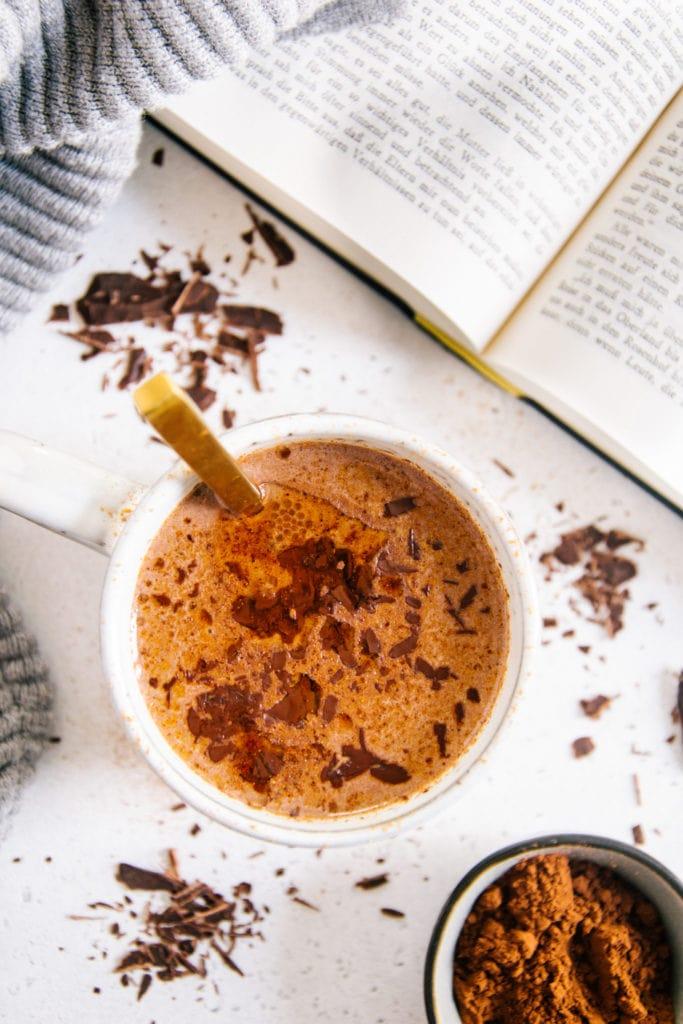 Eine Tasse Kakao von oben fotografiert auf hellem Untergrund mit Kakaopulver darauf. Goldener Löffel in der Tasse, aufgeschlagenes Buch in der rechten oberen Ecke des Bildes.