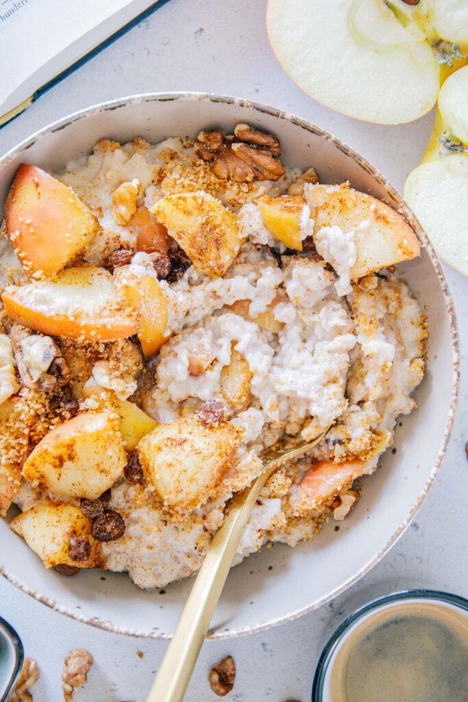 Mit einem goldenen Löffel durchgerührter Apfelstrudel-Porridge. Nahaufnahme von oben, sodass die cremige Konsistenz deutlich sichtbar ist.