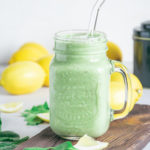 Ein Glas Grüner Smoothie für die Darmgesundheit auf einem rustikalen Brett. Set verziert mit Spinatblättern, Zitronenstücken und Zitronen im Hintergrund. Glasstrohhalm im Smoothie.