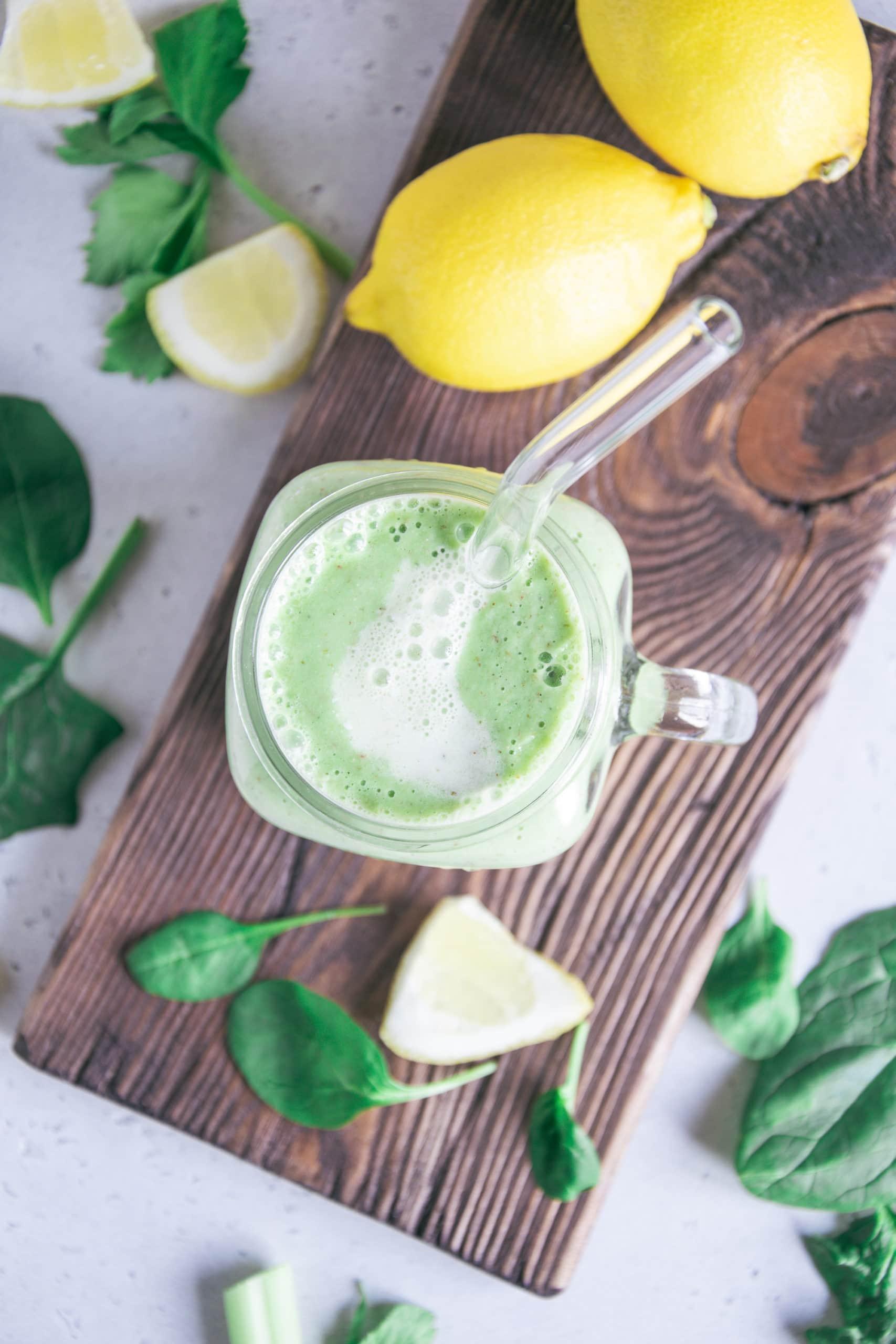 Ein Glas Grüner Smoothie für die Darmgesundheit von oben fotografiert. Rustikales Holzbrett als Untergrund. Smoothie marmoriert mit Mandelmilch. Spinatblätter und Zitronen als Dekoration.