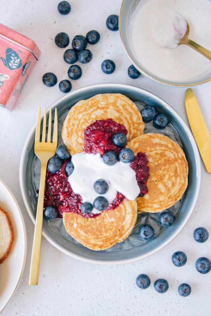 Gesunde glutenfreie Hafer-Chai-Pancakes mit Apfel-Beerenmus und Vanillejoghurt von oben fotografiert auf einem blauen Teller mit einer goldenen Gabel.