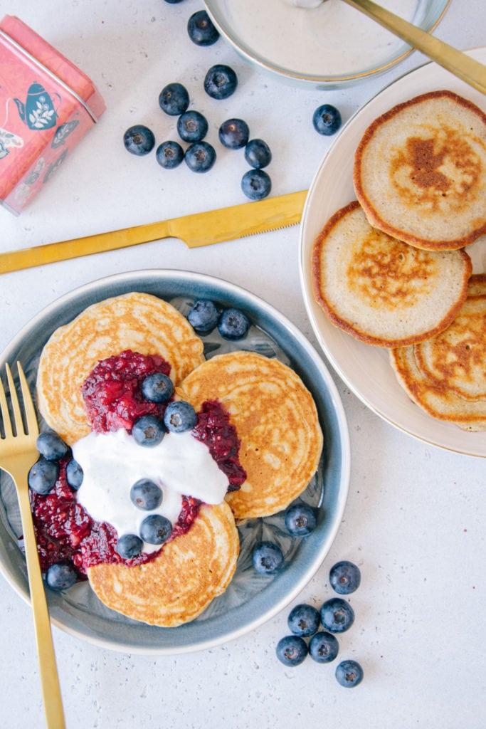 Gesunde glutenfreie Hafer-Chai-Pancakes auf zwei Tellern von oben fotografiert. Ein Teller von rechts angeschnitten. Goldenes Besteck und Heidelbeeren als Verzierung.
