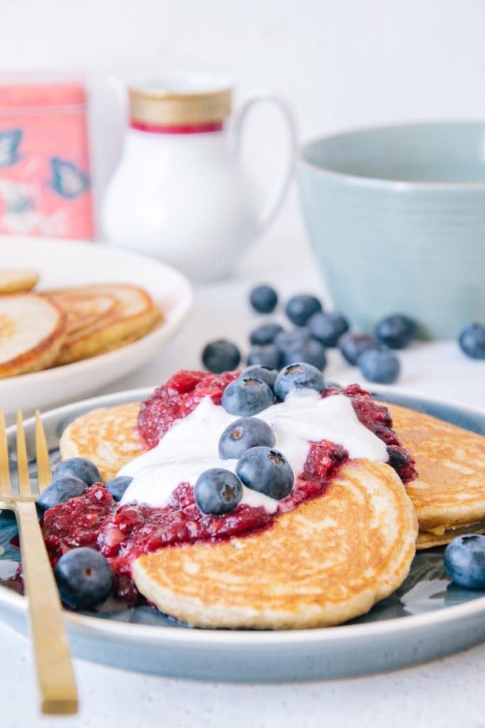 Gesunde glutenfreie Hafer-Chai-Pancakes aus der Nähe auf Augenhöhe fotografiert, mit Fokus auf dem Topping aus Apfel-Beerenmus, Vanillejoghurt und Heidelbeeren.