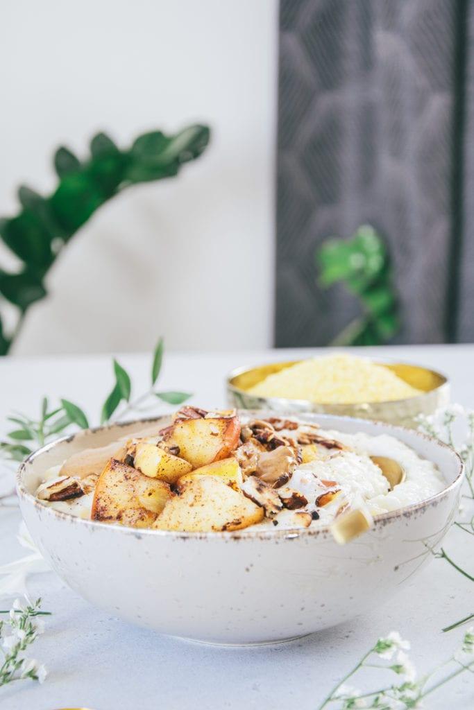 Hirse-Porridge mit Bratapfel in einer grauen Schüssel auf Augenhöhe fotografiert. Der goldene Löffel im Porridge lädt zum Essen ein.