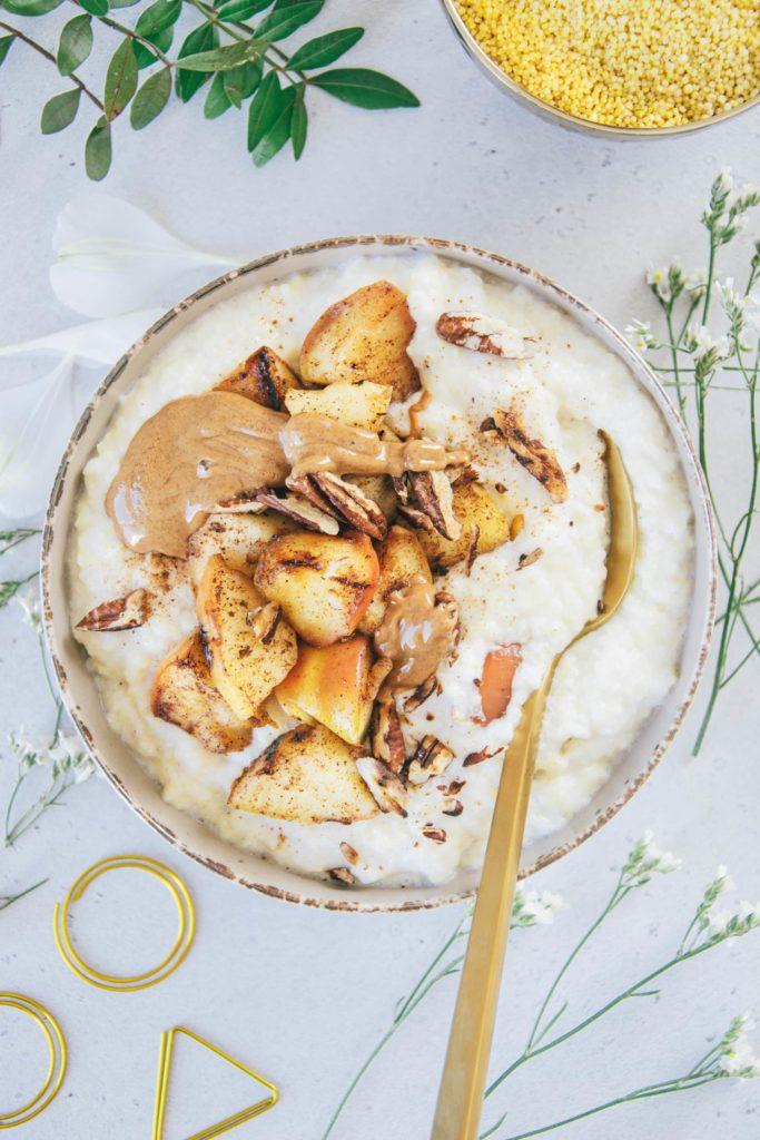 Eine Schüssel Hirse-Porridge mit Bratapfel von oben fotografiert auf hellem Untergrund. Topping aus Bratapfel, Mandelmus und gerösteten Pekannüssen.