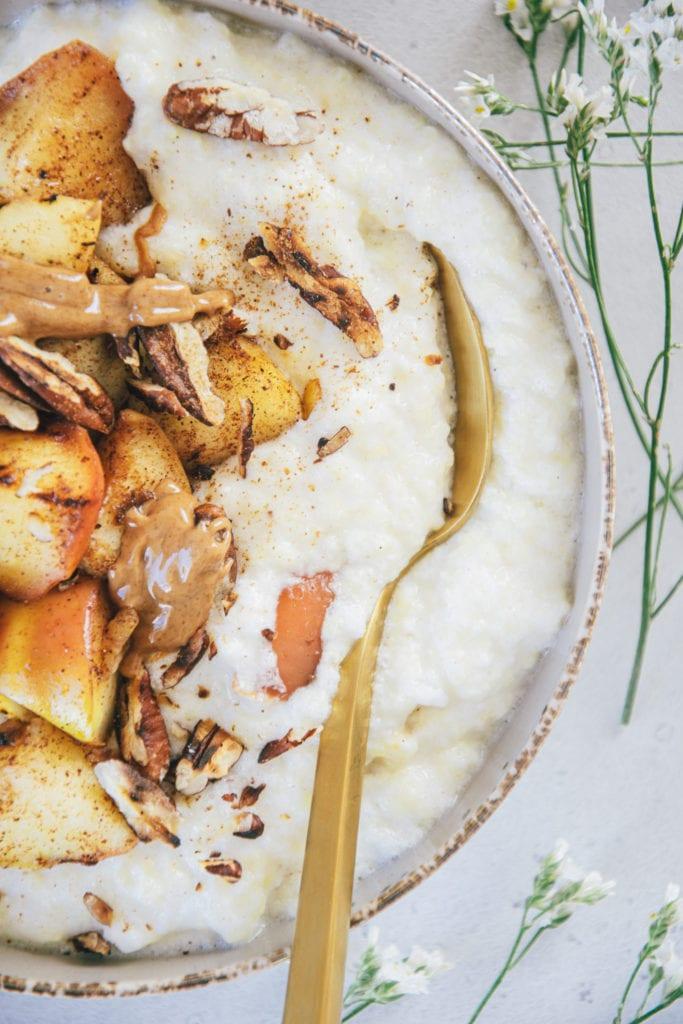 Nahaufnahme von Hirse-Porridge mit Bratapfel von oben. Schüssel von links angeschnitten. Ein goldener Löffel steckt seitlich im Porridge, sodass man sieht, wie cremig es ist.
