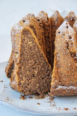 Angeschnittener Low carb Mohnkuchen auf Augenhöhe fotografiert. Ein Stück lehnt in der Schnittöffnung des Gugelhupfs, sodass alle Details gut erkennbar sind.