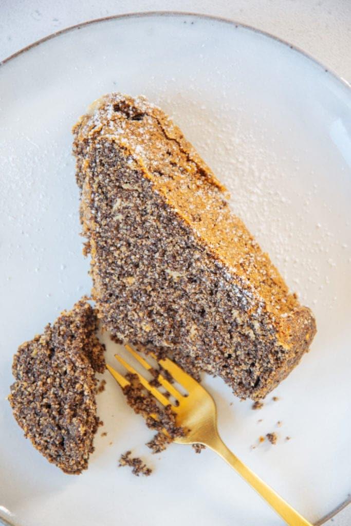 Ein Stück saftiger Low carb Mohnkuchen liegend von oben aus der Nähe fotografiert. Eine kleine goldene Gabel hat ein Stück Kuchen abgestochen.