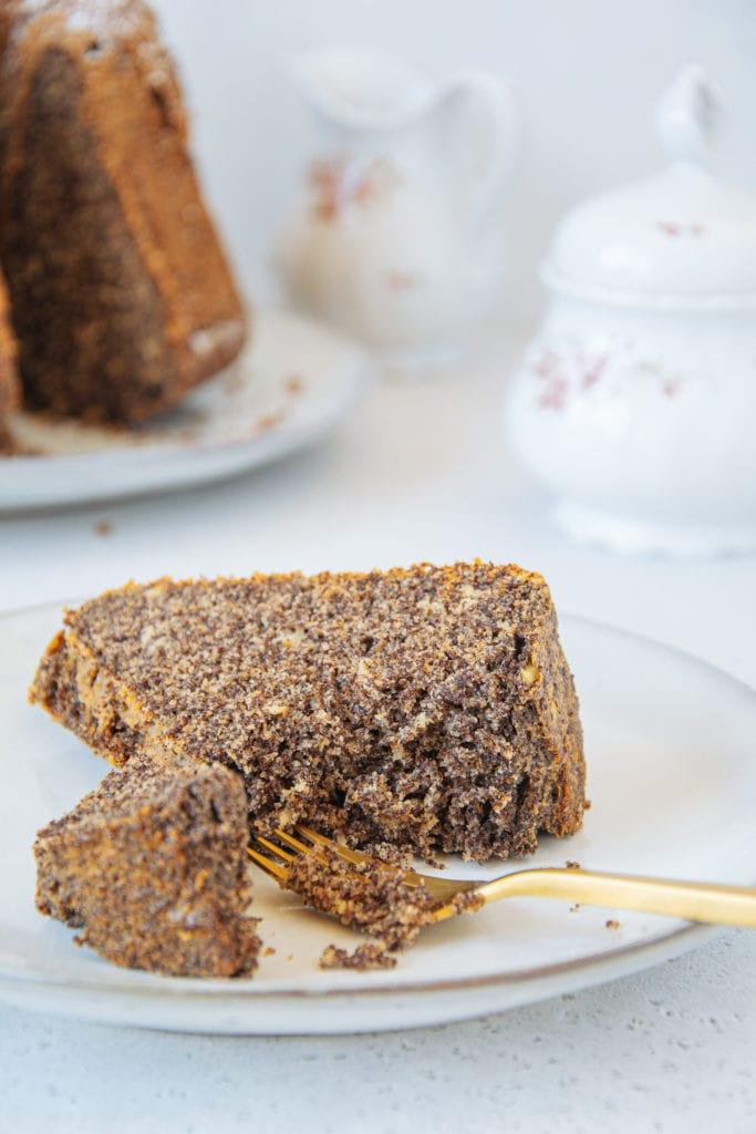 Ein Stück zuckerfreier Low carb Mohnkuchen auf Augenhöhe auf einem Teller, von einer goldenen Gabel angestochen, sodass die saftige Teigstruktur gut erkennbar ist.