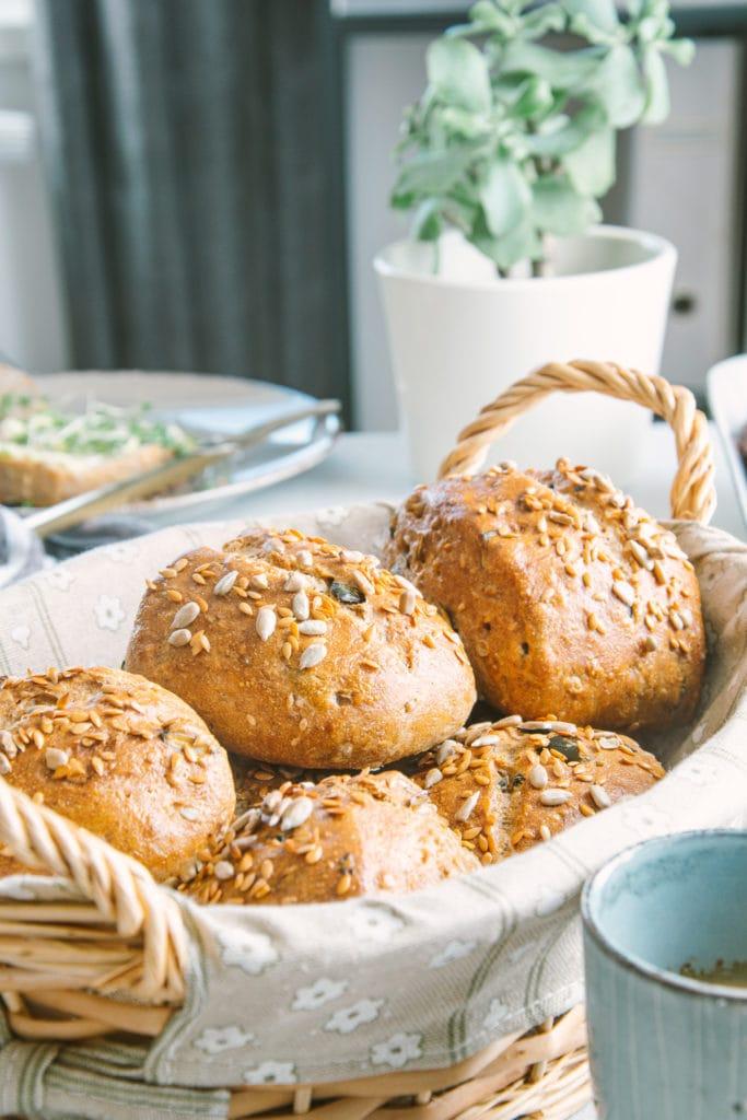 Geflochtener Brotkorb mit frischen Dinkel-Körnerweckerln. Aufnahme im 45-Grad-Winkel. Eine Grünpflanze und ein Teller mit einem aufgeschnittenen Weckerl im Hintergrund.