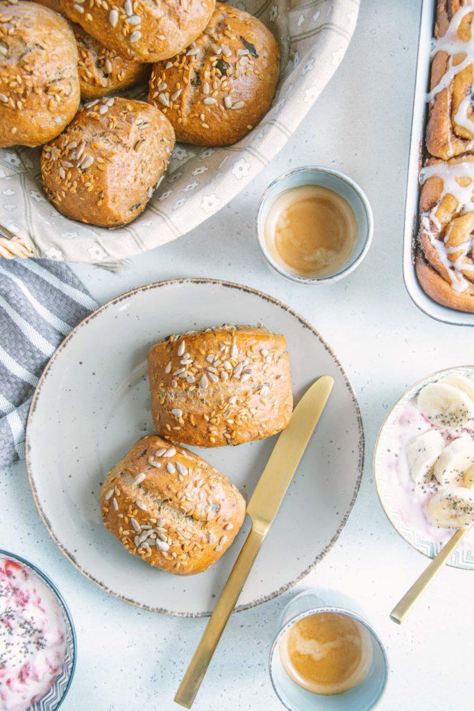 Zwei Dinkel-Körnerweckerl auf einem grauen Teller mit einem goldenen Messer. Zwei Müslischüsseln, zwei Espressotassen, ein Brotkorb und eine Auflaufform mit Zimtschnecken am Bildrand angeschnitten rundherum. Aufnahme von oben.