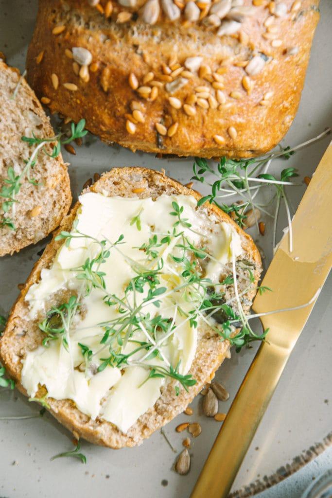 Ein aufgeschnittenes Dinkel-Körnerweckerl auf einem grauen Teller. Die Unterseite ist mit Butter bestrichen und mit Kresse bestreut. Goldenes Messer daneben. Aufnahme von oben.