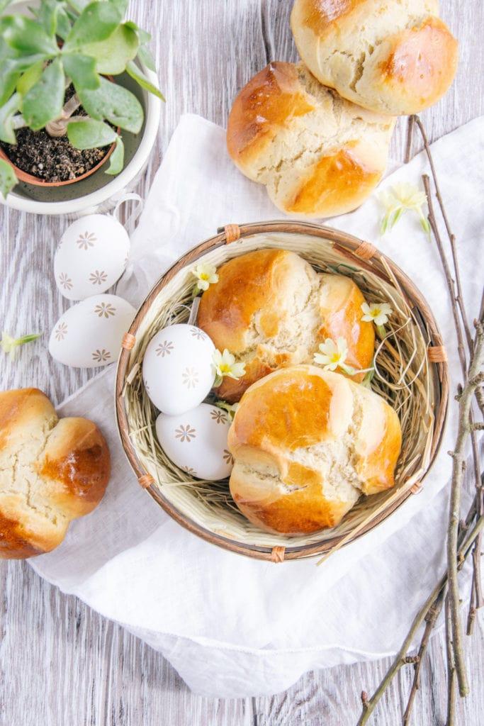 Dinkel-Osterpinzen ohne Zucker auf einem hellen, frühlingshaften Set mit Osternest, Zweigen und Schlüsselblumen. Aufnahme von oben.