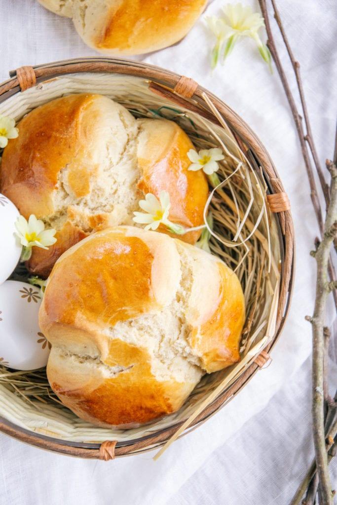 Zwei Dinkel-Osterpinzen ohne Zucker in einem geflochtenen Osternest. Mit Schlüsselblumen und Zweigen dekoriert.