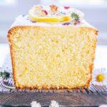 Aufnahme auf Augenhöhe vom angeschnittenen saftigen Zitronenkuchen. Die feinporige und dichte Teigstruktur ist deutlich erkennbar. Kuchen mit Zitronenscheiben und Gänseblümchen verziert.