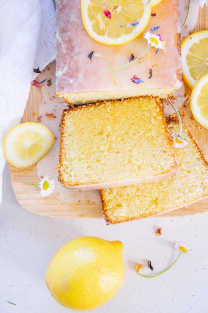Nahaufnahme von oben von zwei Stücken Zitronenkuchen, die vom ganzen Kuchen auf einem Brett abgeschnitten wurden und neben dem Kuchen aufgefächert liegen. Heruntergelaufene Zitronenglasur auf dem Brett und ganze Zitrone als Verzierung.