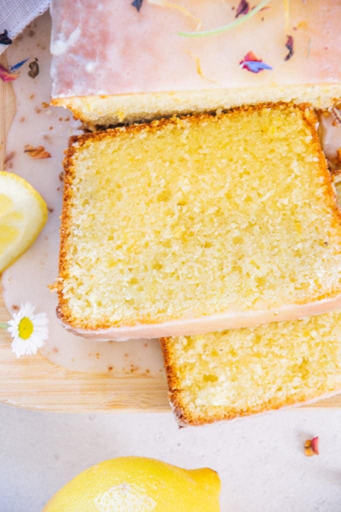 Nahaufnahme von oben von zwei Stücken Zitronenkuchen, die vom ganzen Kuchen auf einem Brett abgeschnitten wurden.