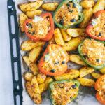 Gefüllte Bulgur-Feta-Paprika mit Ofen-Wedges auf dem Backblech von oben auf hellem Untergrund fotografiert. Blech auf der rechten Seite angeschnitten.
