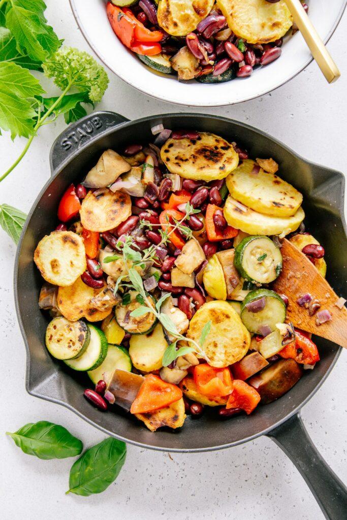 Mediterrane Bratkartoffel-Gemüsepfanne in einer schwarzen Gusseisenpfanne von oben auf hellem Untergrund fotografiert.