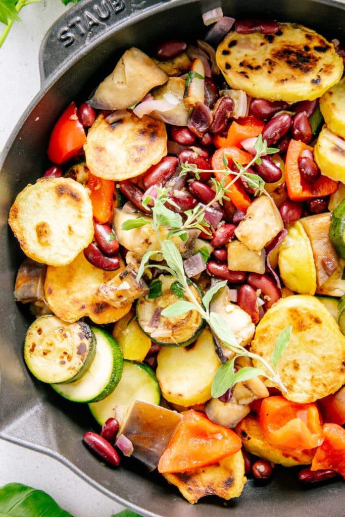 Nahaufnahme von Mediterraner Bratkartoffel-Gemüsepfanne von oben. Kartoffeln, Zucchini, Melanzani, Paprika und Kidneybohnen sind deutlich erkennbar.