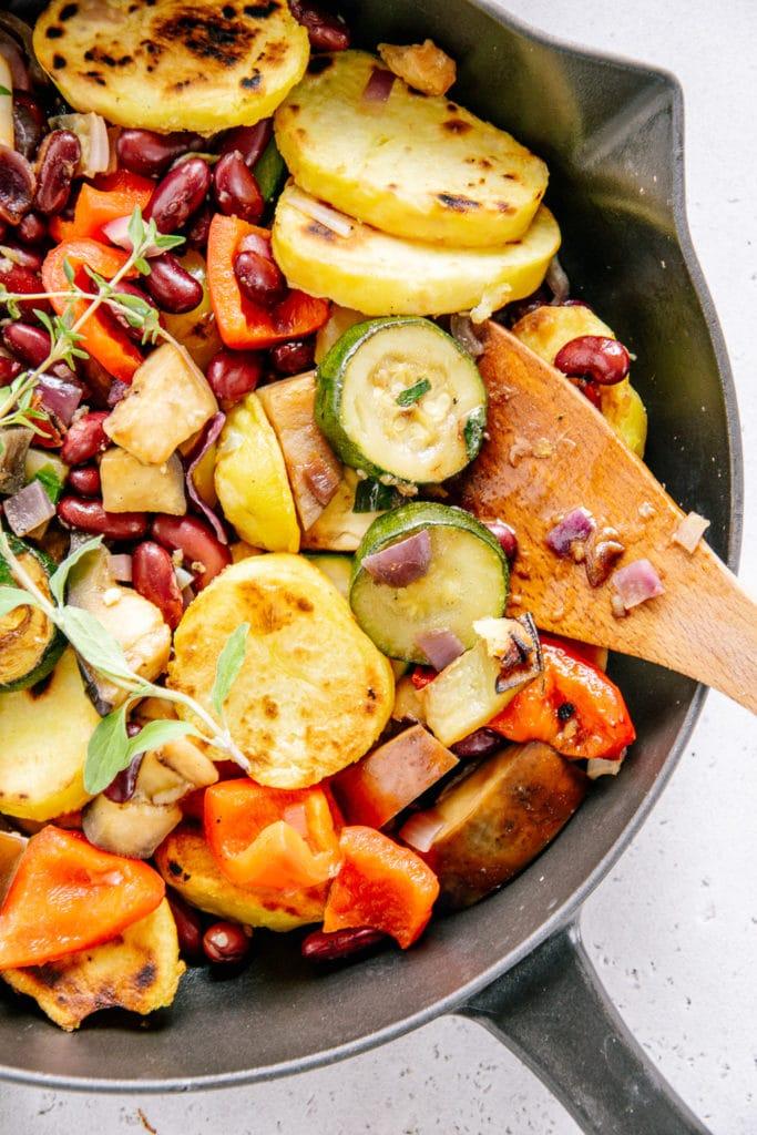 Nahaufnahme von Mediterraner Bratkartoffel-Gemüsepfanne in einer schwarzen Gusseisenpfanne von oben. Hölzerner Pfannenwender im Gemüse.