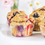 Vegane zuckerfreie Beerenmuffins auf Augenhöhe auf einer weißen Tortenplatte fotografiert