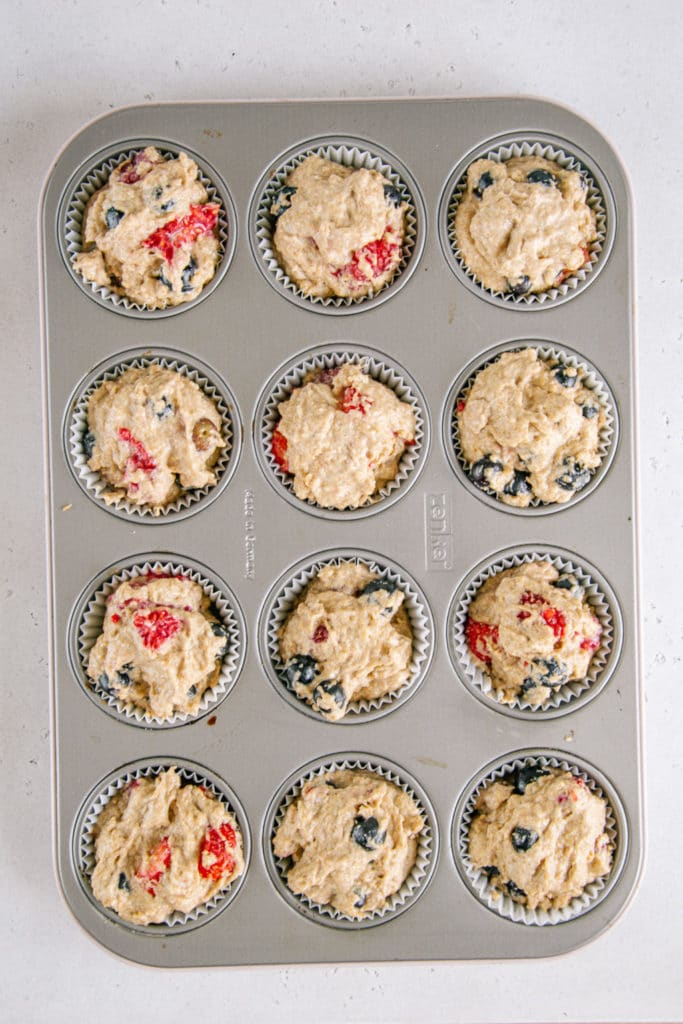 Teig für vegane zuckerfreie Beerenmuffins ins Muffinblech gefüllt. Aufnahme von oben.