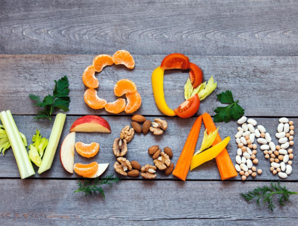 """Die Worte """"GO VEGAN"""" mit Gemüse und Obst auf einem Holzbrett geschrieben"""