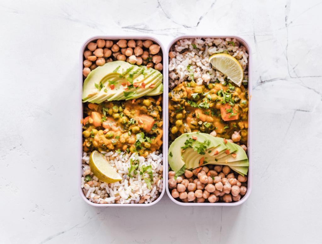 Zwei längliche eckige Lunchboxen mit Kichererbsen, Avocadospalten, Curry und Reis aus der Vogelperspektive auf hellem Untergrund aufgenommen