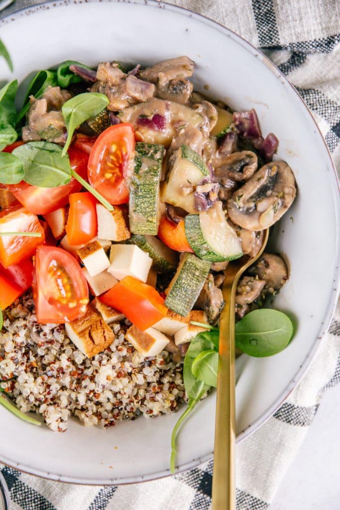 Nahaufnahme aus der Vogelperspektive von cremiger Pilzpfanne mit Zucchini, Räuchertofu, Tomaten und Quinoa.