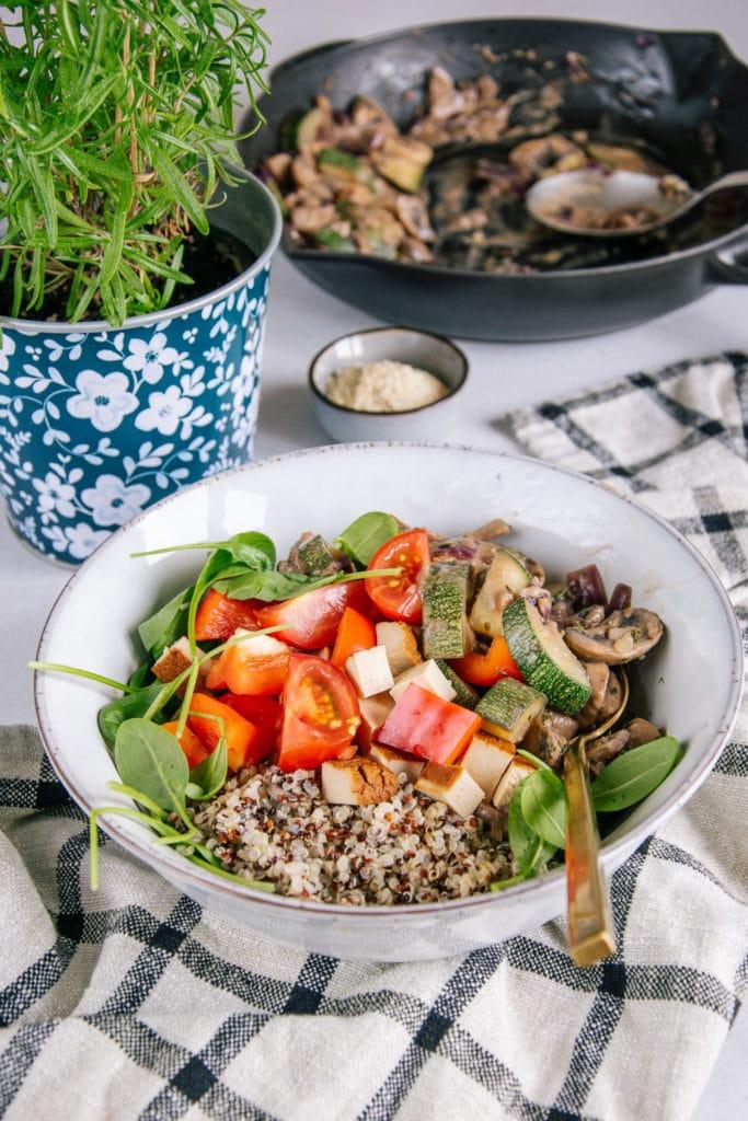 Cremige vegane Pilzpfanne mit Zucchini, Räuchertofu, Tomaten und Quinoa in einer graublauen Schüssel auf einem karierten Küchentuch. Aufnahme im 45-Grad-Winkel. Blumentopf mit Thymian als Dekoration.